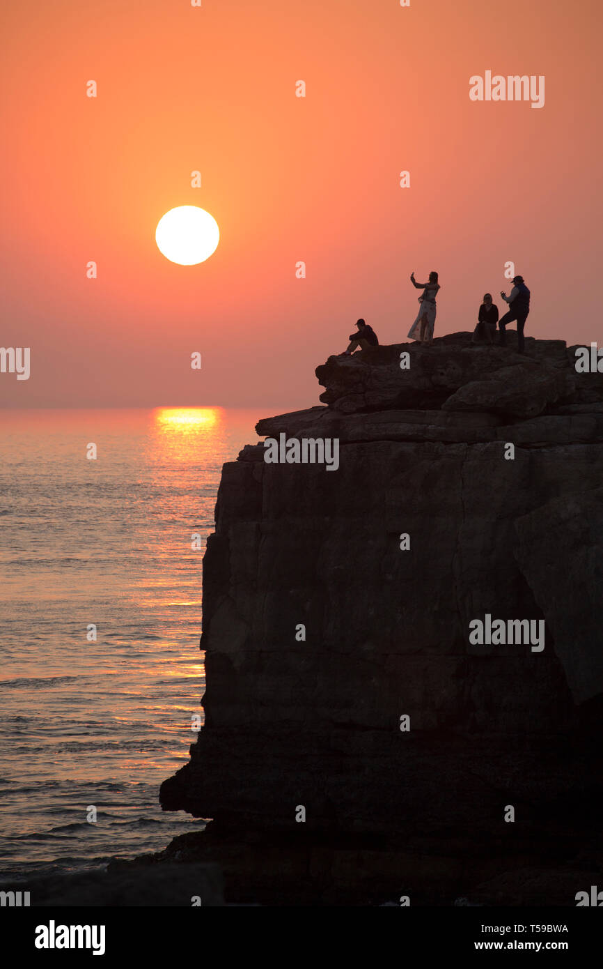 People taking pictures and sitting on top of the famous tourist attraction of Pulpit Rock on the tip of Portland Bill on the Isle of Portland as the s - Stock Image