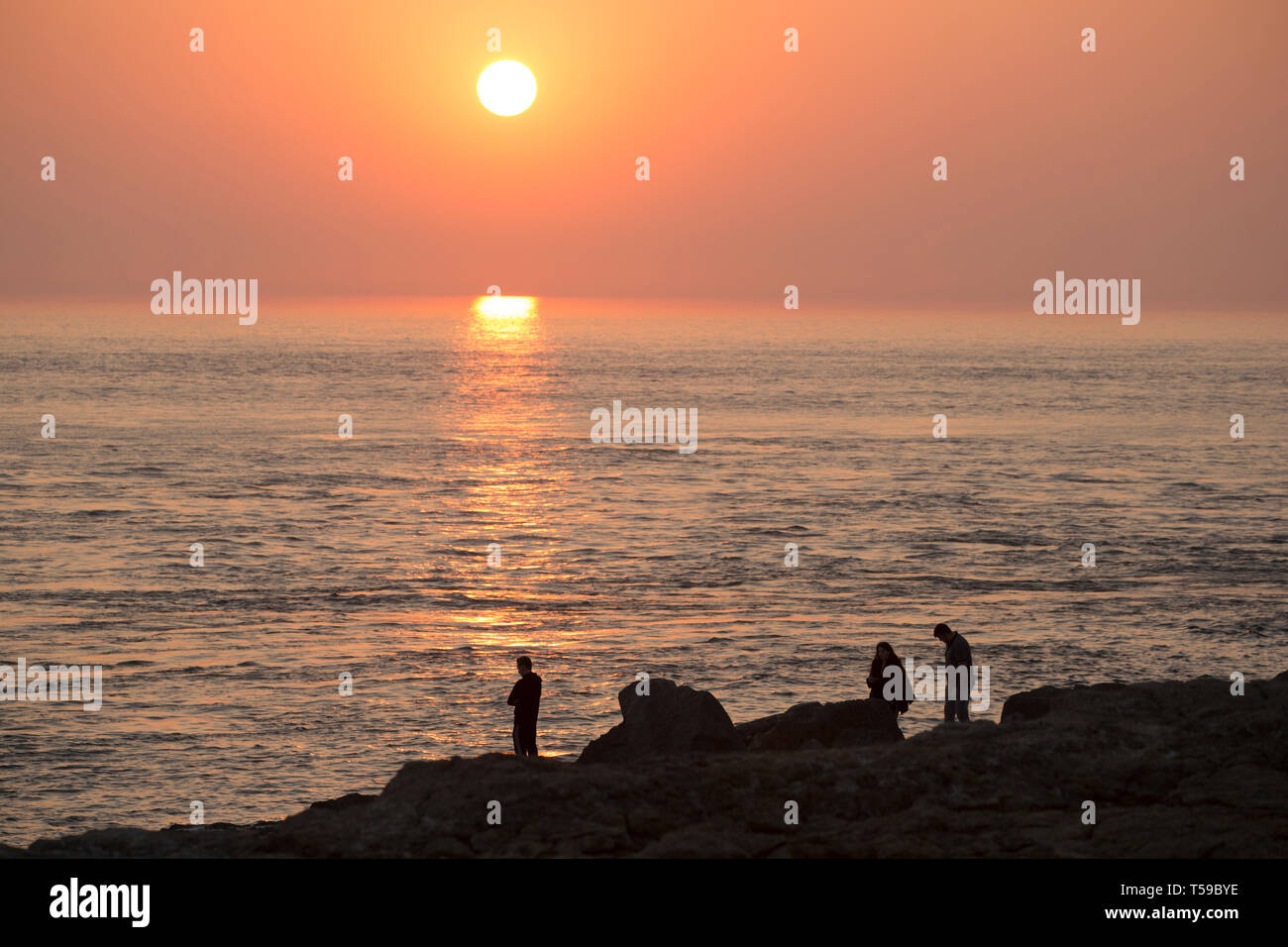 People standing on the rocky shore of Portland Bill close to the famous attraction of Pulpit Rock on the tip of the Isle of Portland as the sun goes d - Stock Image