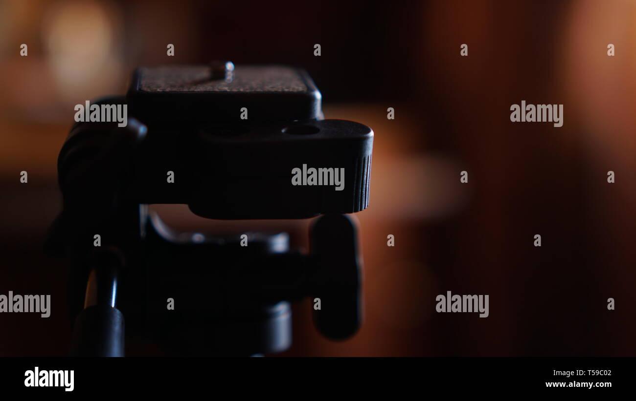 Tripod for camera. Three-legged tripod. Screwing for the camera. Camera control pen. Blurred background - Stock Image