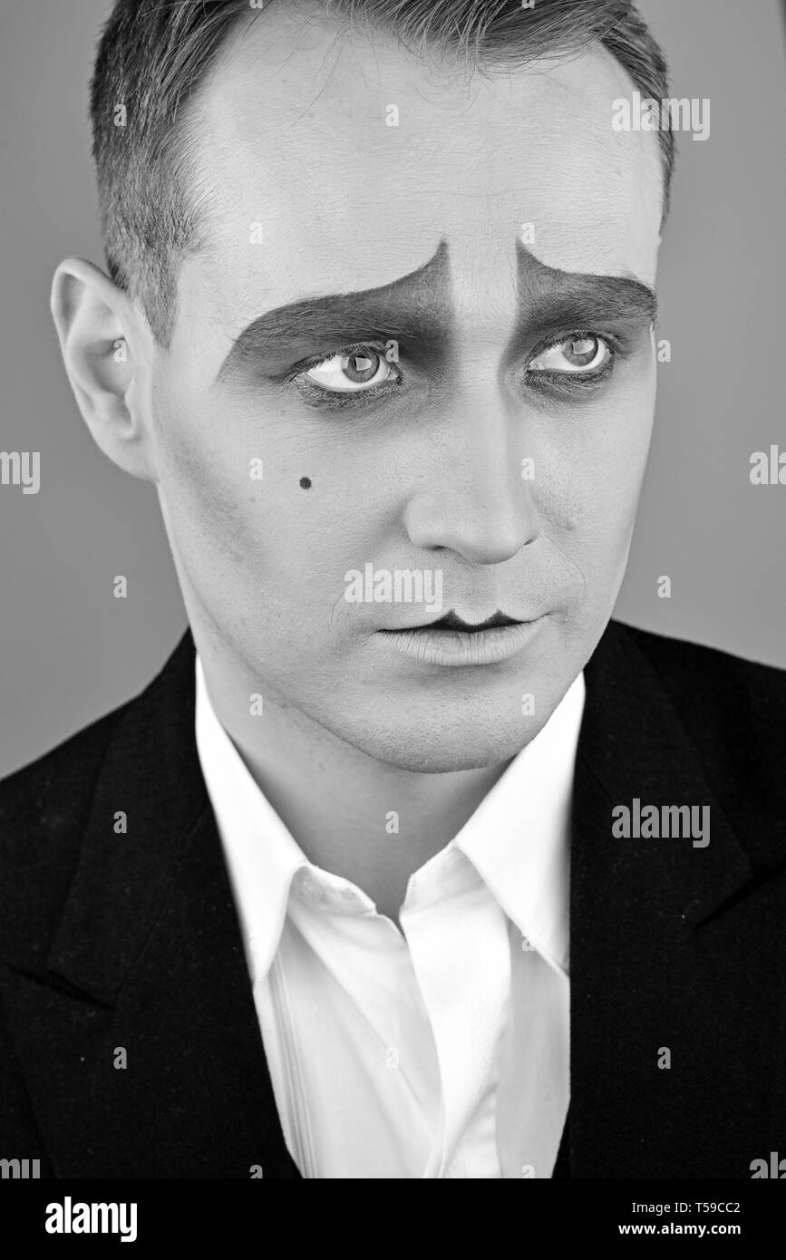 Serious and genuine. Drama or tragedian performer. Theatre actor miming. Mime with face paint. Mime artist. Man with mime makeup. Stage actor playing - Stock Image