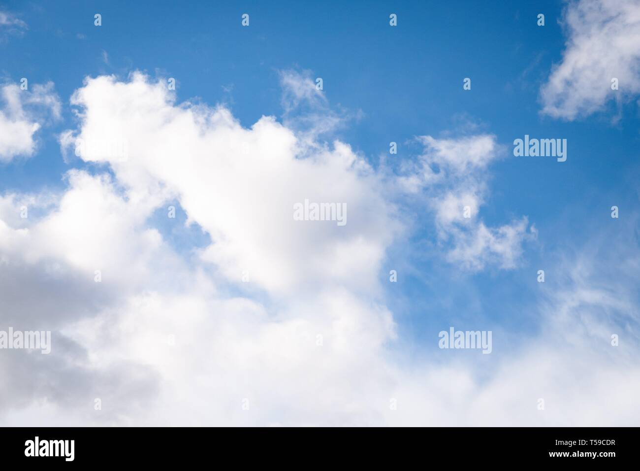 White fluffy clouds on a blue sky background Stock Photo