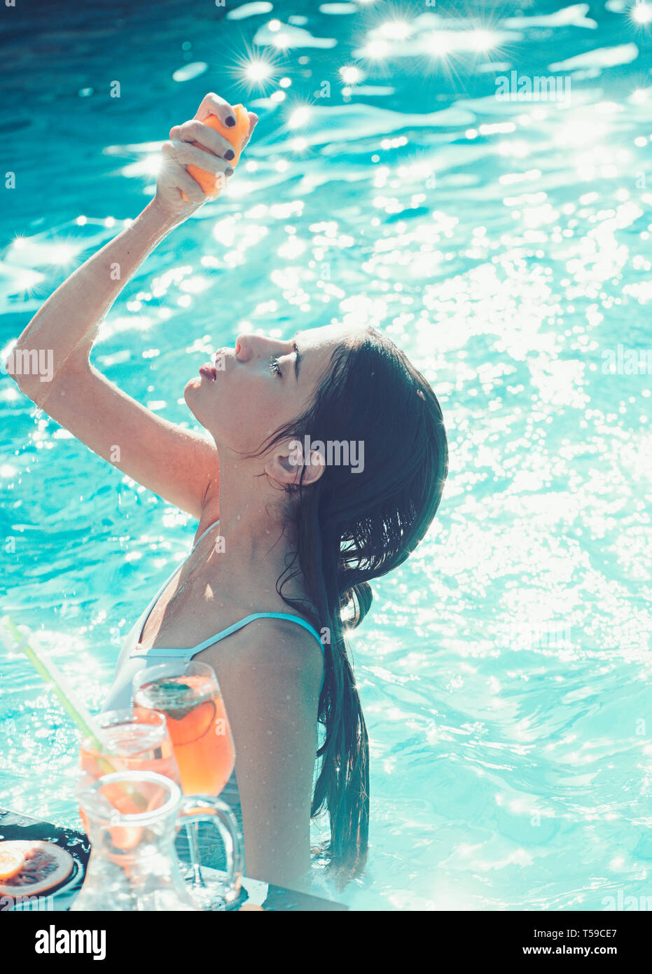 384e8c0783d68 Joyful woman having fun bathing in hotel resort spa pool and drinking juice  and cocktail on