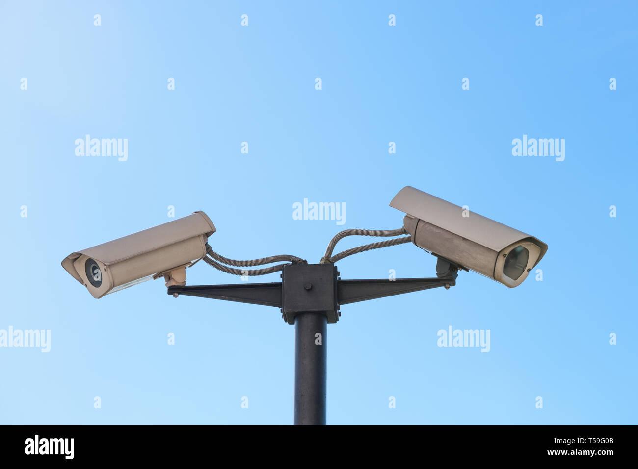 CCTV surveillance cameras on pillar mount over blue sky background - Stock Image