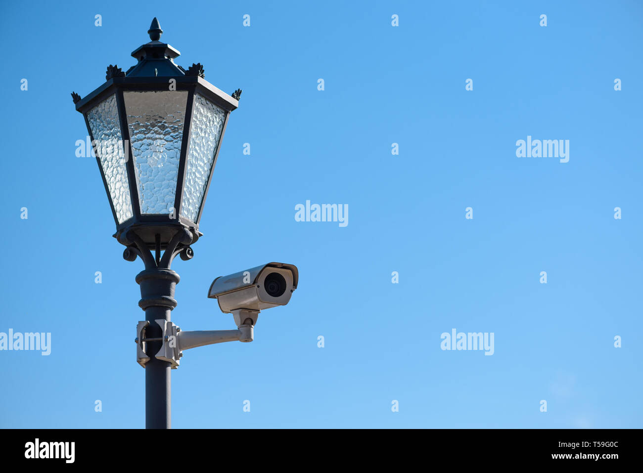 CCTV surveillance camera mounted on vintage street lantern over blue sky background - Stock Image
