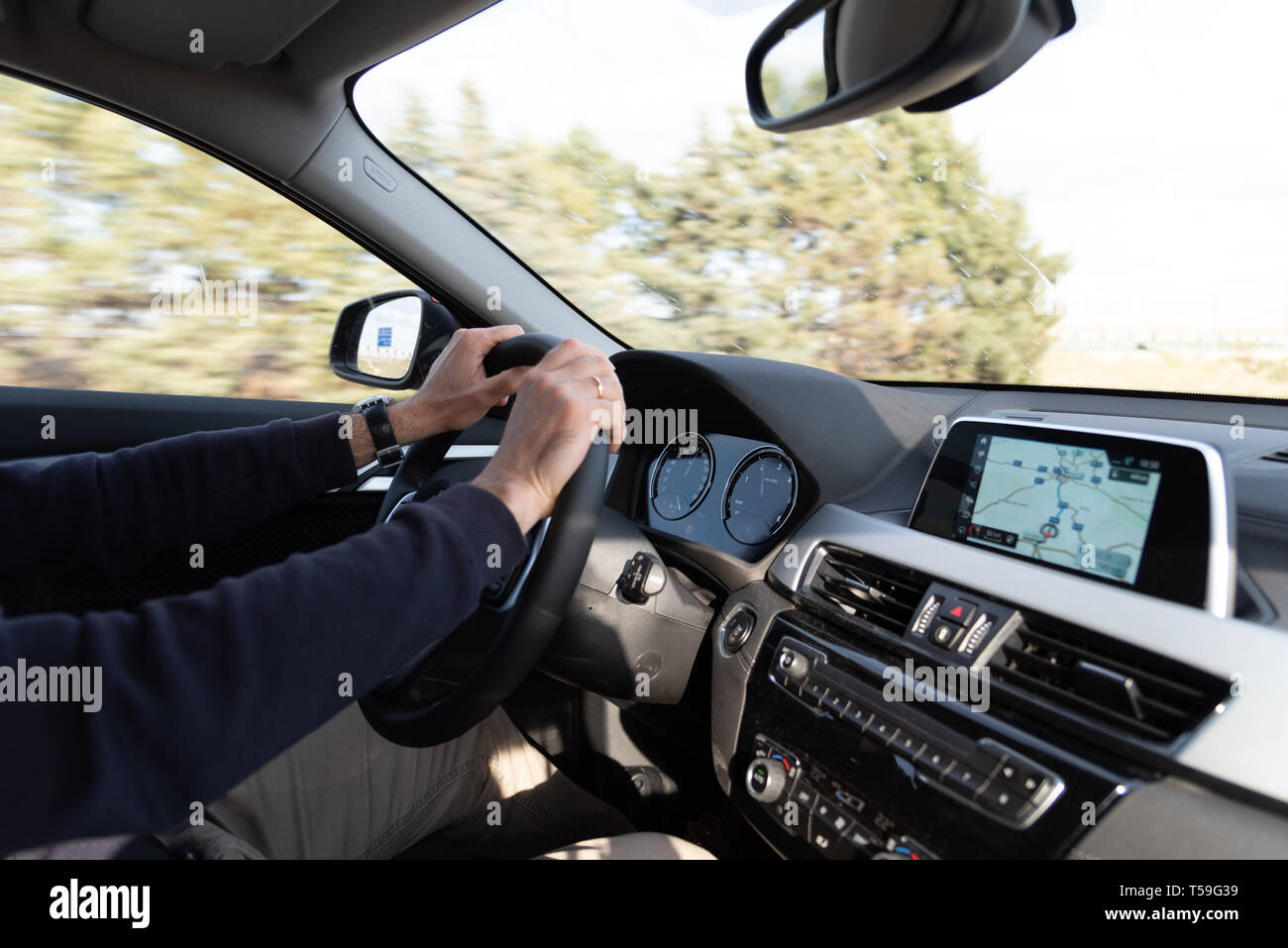 Madrid, Spain - April 1, 2019: Side view of man driving BMW X2 car, with his hands on the steering wheel, using a satelite navigation GPS - Stock Image