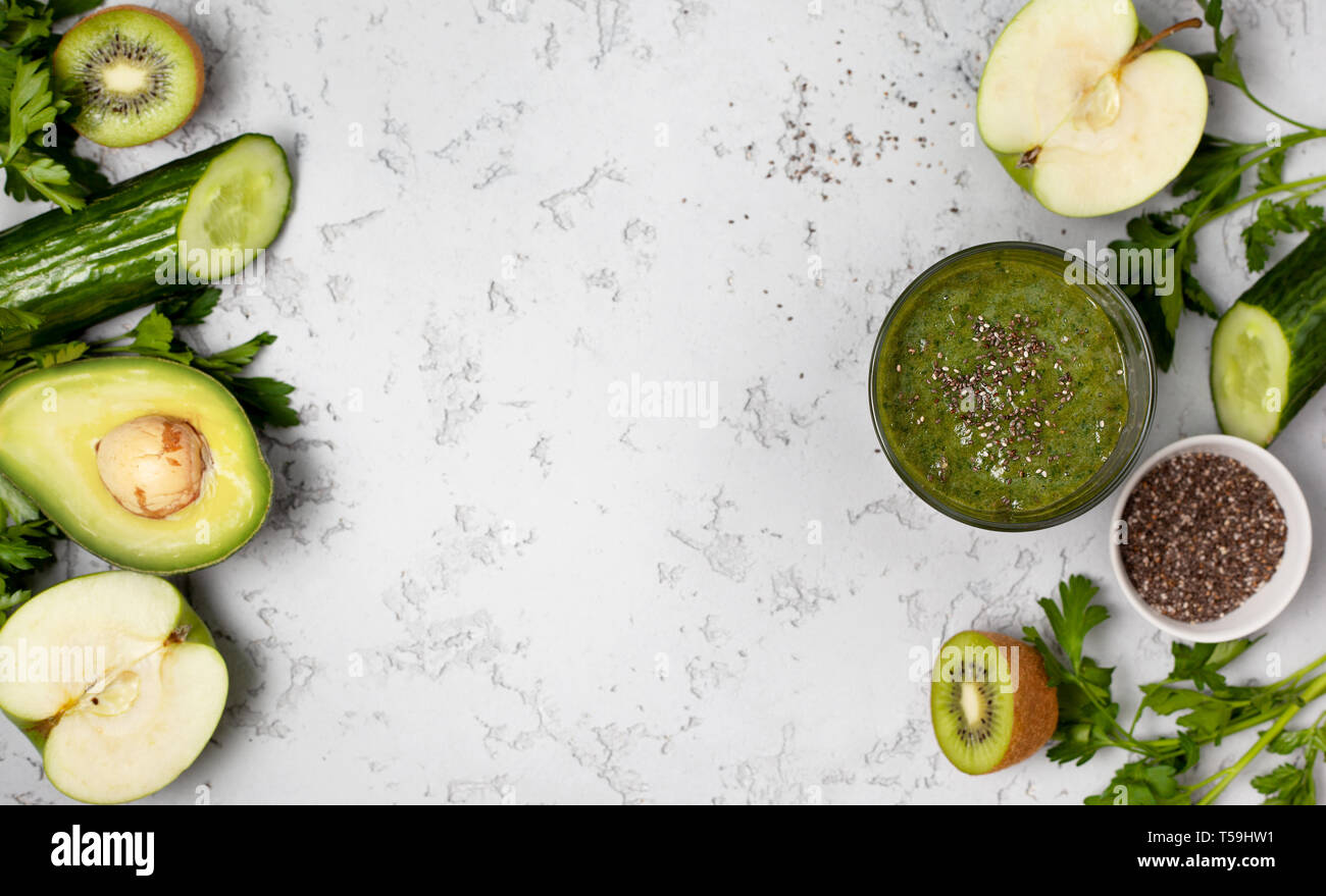 green smoothie in a glass, fresh fruits and vegetables on a gray background. view from above.  copy space Stock Photo