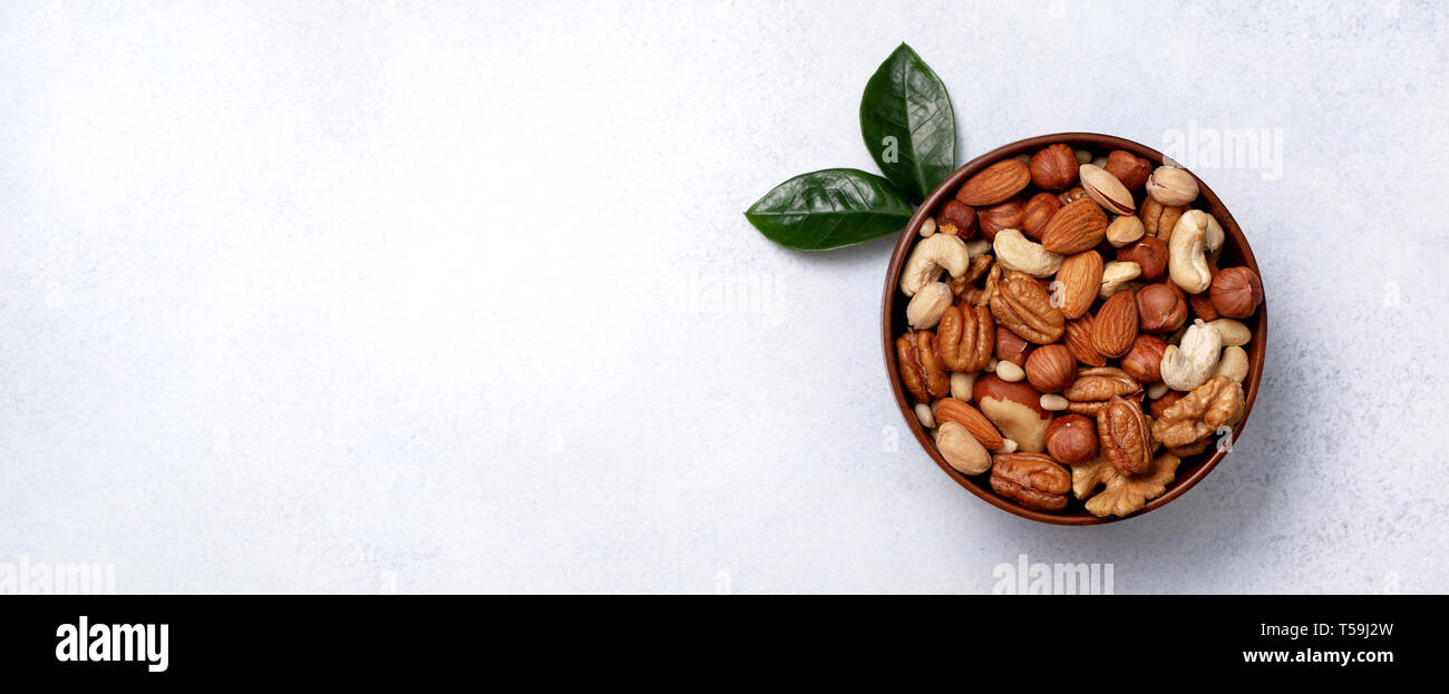 mix of nuts in a wooden bowl on a light background. view from above. copy space. banner - Stock Image