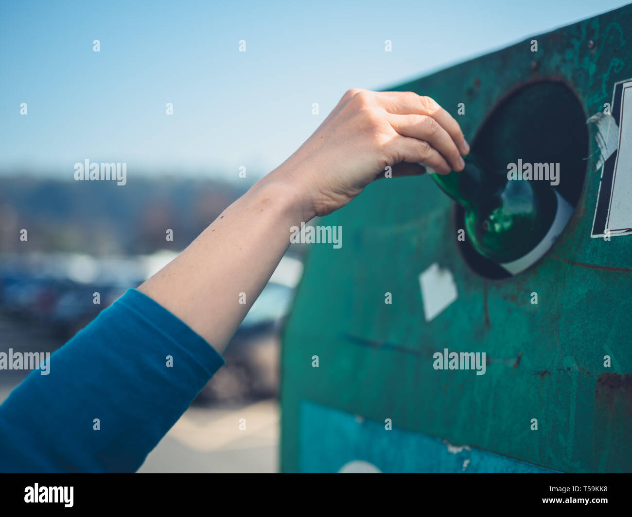 A young woman is recycling a glass bottle at a bottle bank - Stock Image