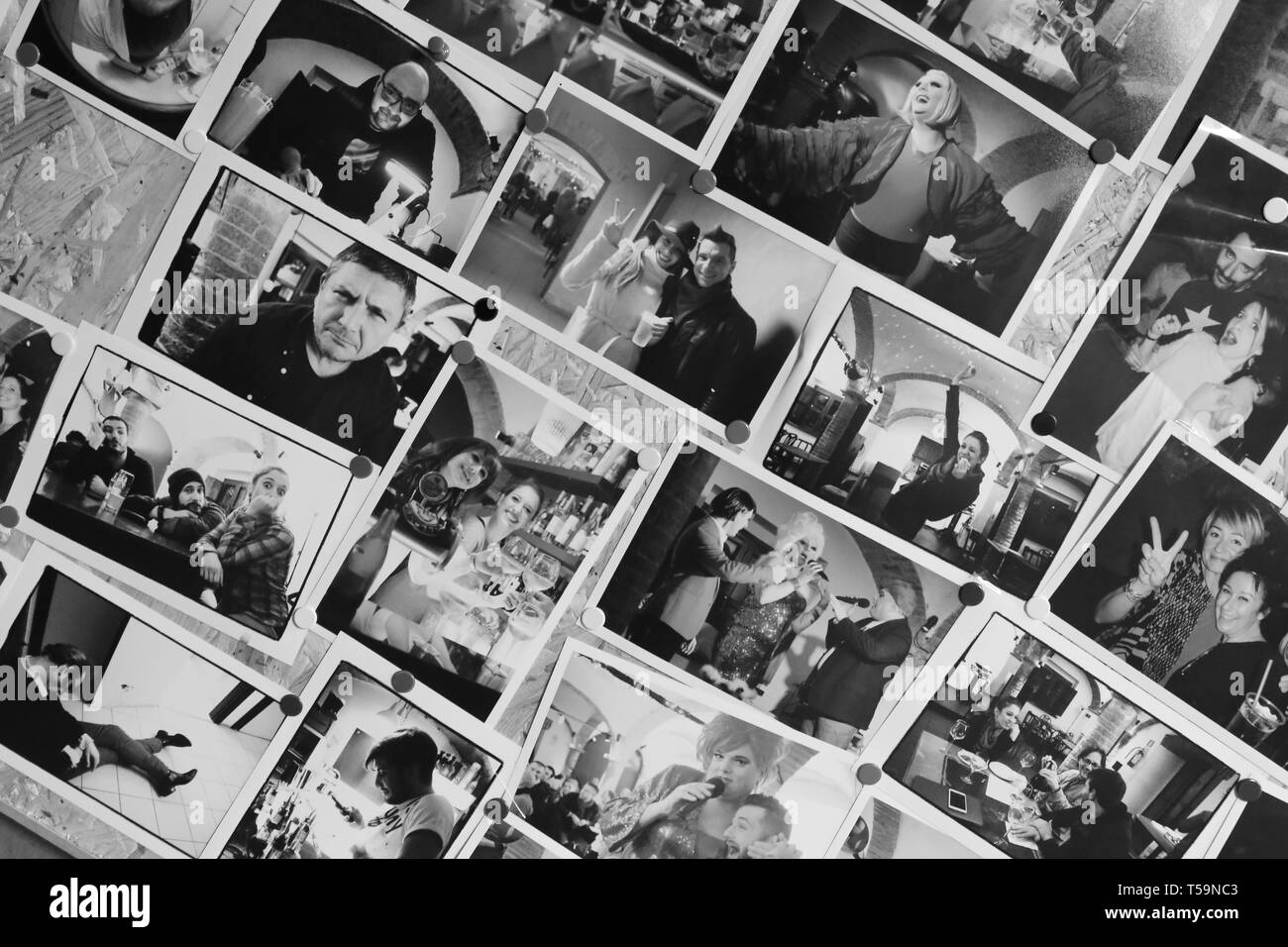 Photographs in black and white of various people on the wall - Stock Image