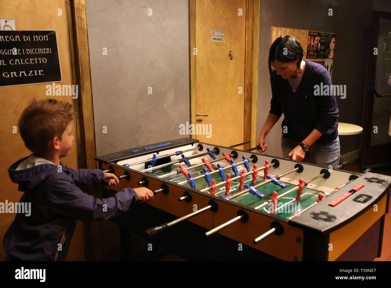 one adult and one boy in the background play table football in a bar - Stock Image
