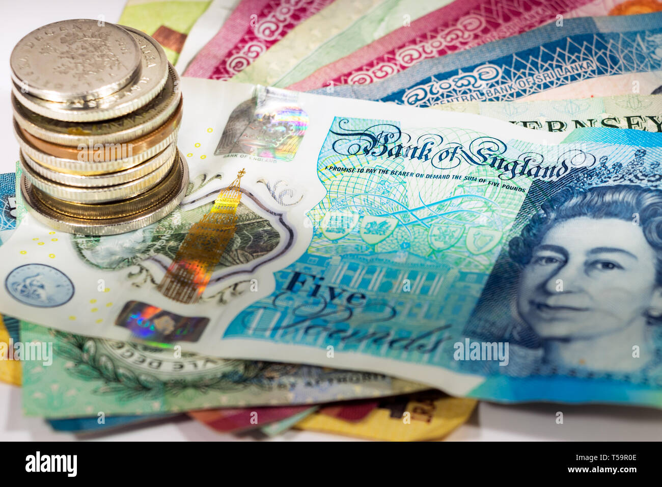 A five pound new polymer banknote from UK with a pile of coins, focus on the bank of england phrase. - Stock Image