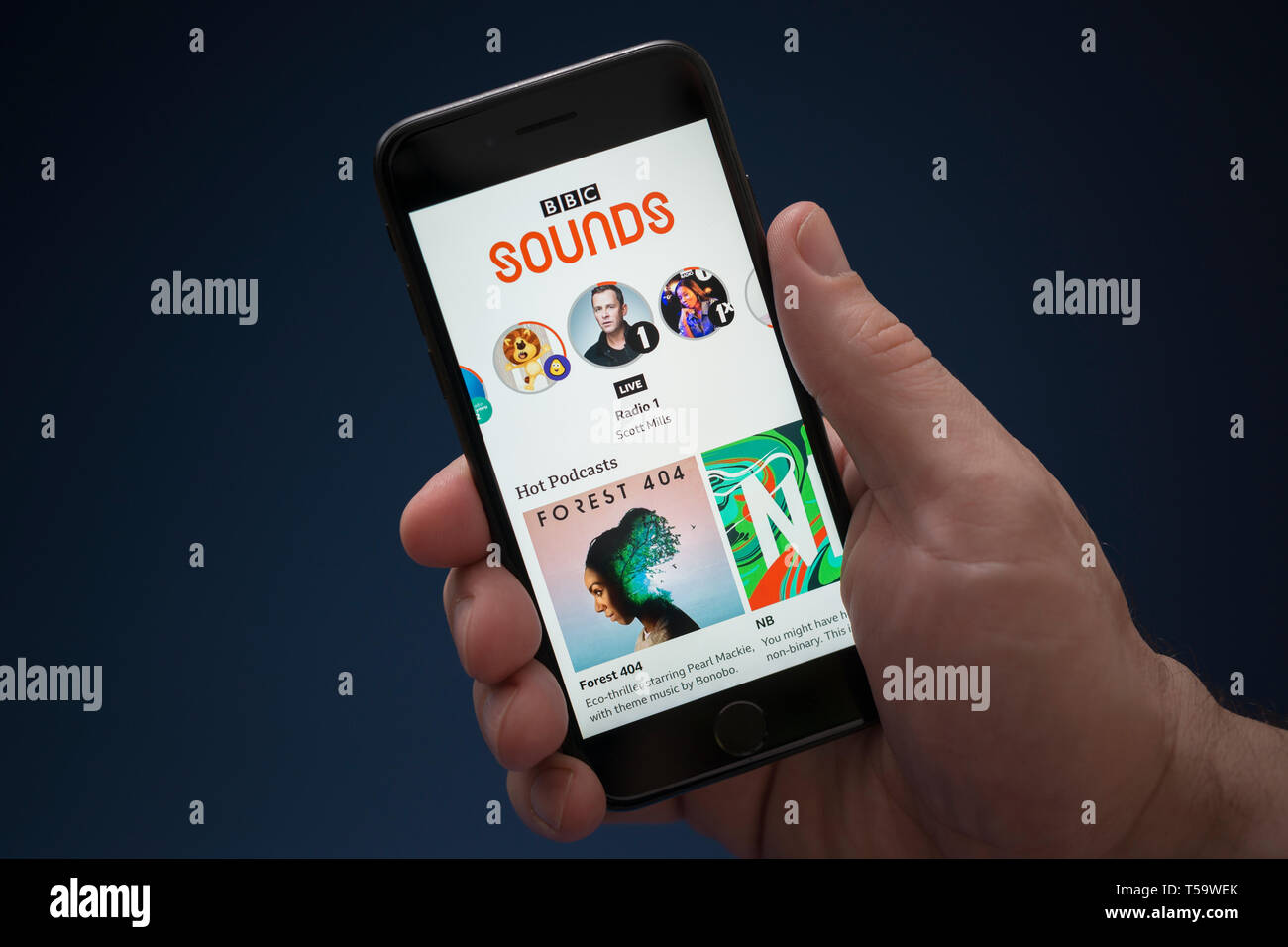 A man looks at his iPhone which displays the BBC Sounds logo (Editorial use only). - Stock Image