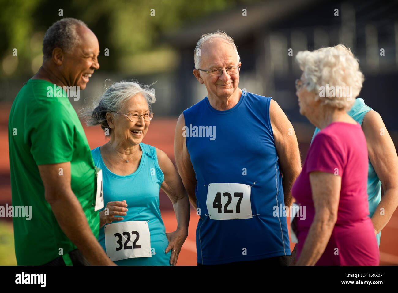 Happy seniors laughing and talking before an athletics event. - Stock Image