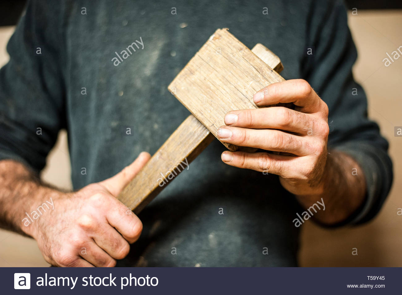 Crafter with a vintage wooden mallet - Stock Image