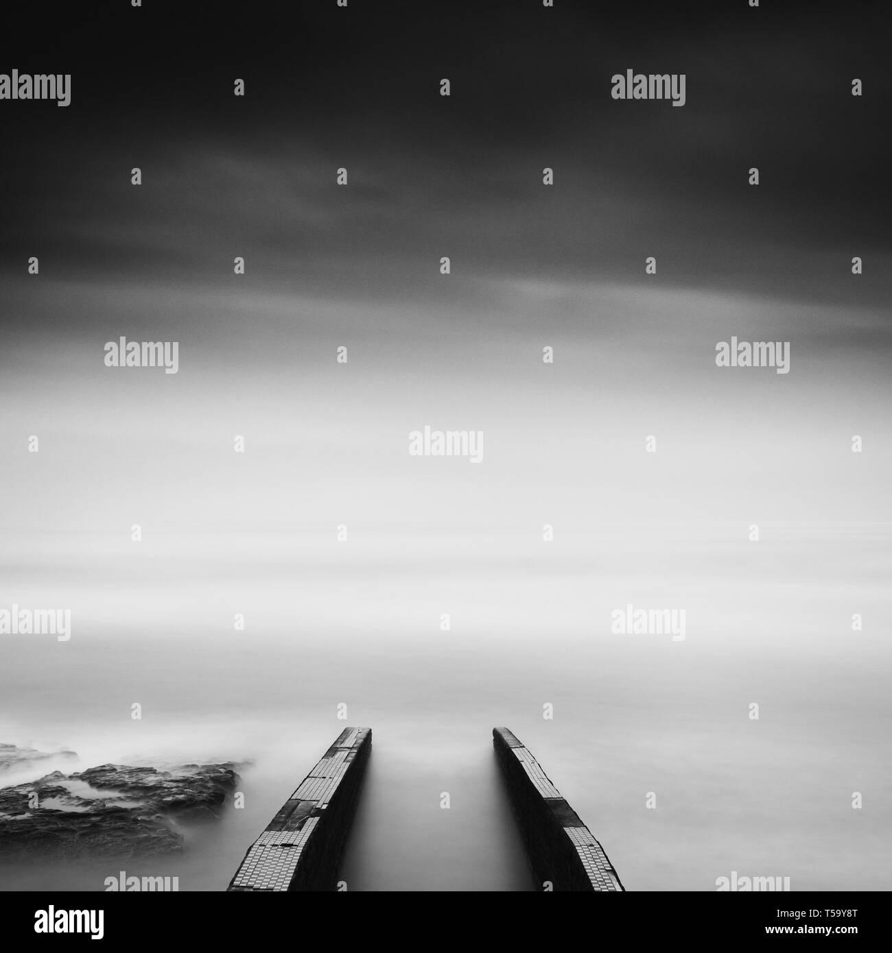 Long exposure of pier in the sea and dramatic sky in Inamuragasaki - Stock Image