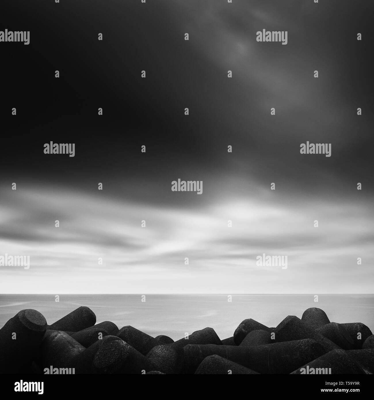 Long exposure of tetrapods in the sea and dramatic sky, Inamuragasaki - Stock Image