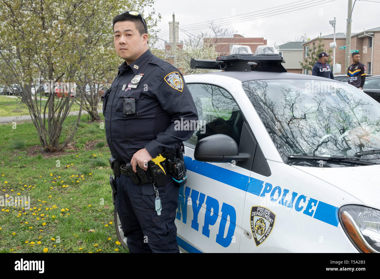 Portrait of a Chinese American police office on duty at a cricket tournament in Baisley Pond Park in Jamaica, Queens, New York City. Stock Photo