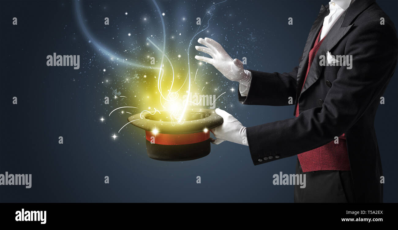 Magician hand conjure with wand  light from a black cylinder - Stock Image