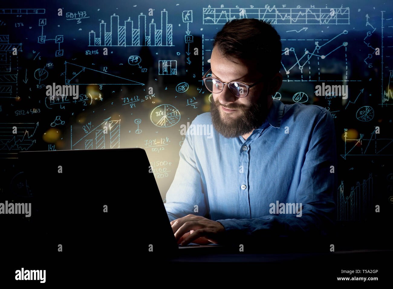 Young handsome businessman working late at night in the office with blue calculations in the background - Stock Image