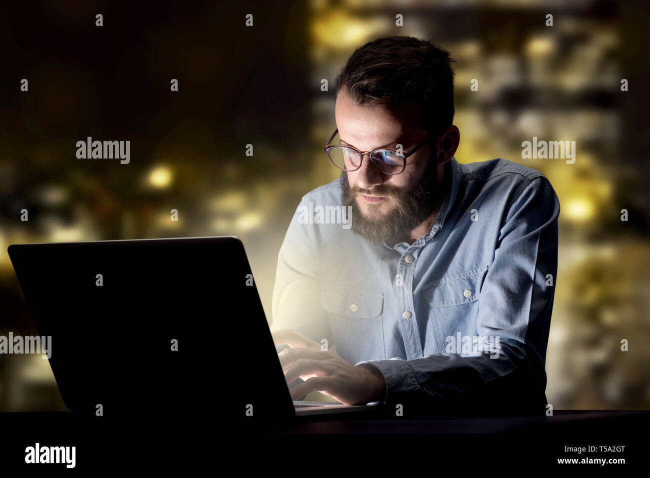 Young handsome businessman working late at night in the office with city lights in the background - Stock Image