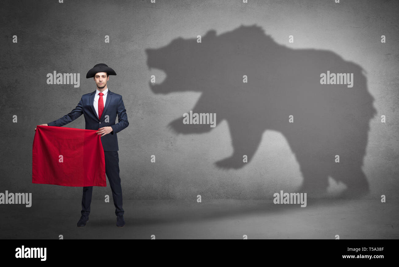 Businessman standing with red cloth in his hand and big bear shadow on his background  - Stock Image