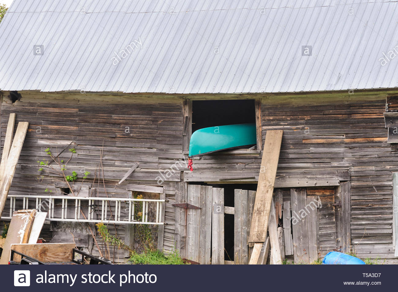 Canoe sticking out of upper story of old wood barn - Stock Image
