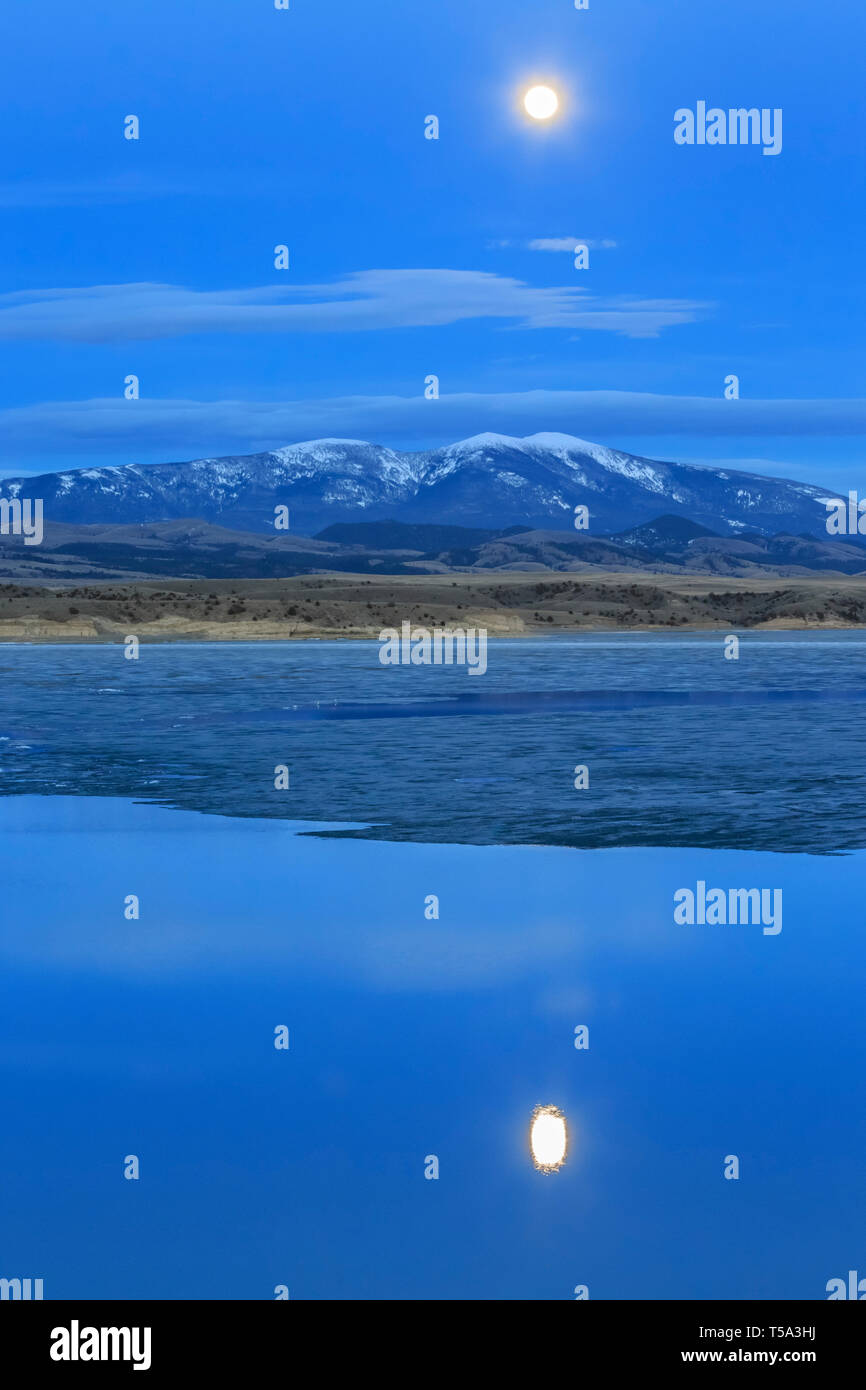 full moon rising behind mount baldy above ice breakup on canyon ferry lake near townsend, montana - Stock Image