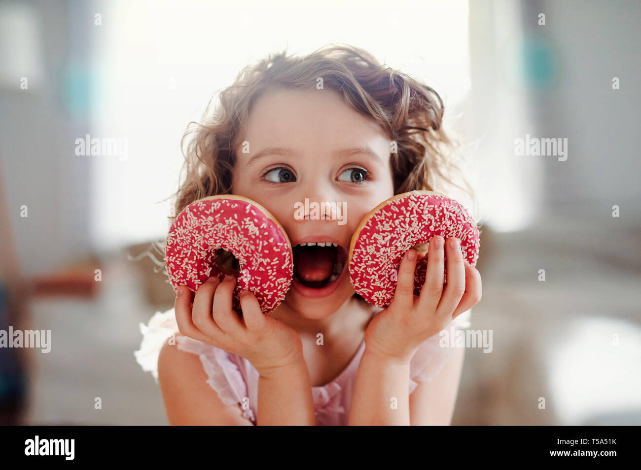 A portrait of small girl with two doughnuts at home, looking at camera. - Stock Image