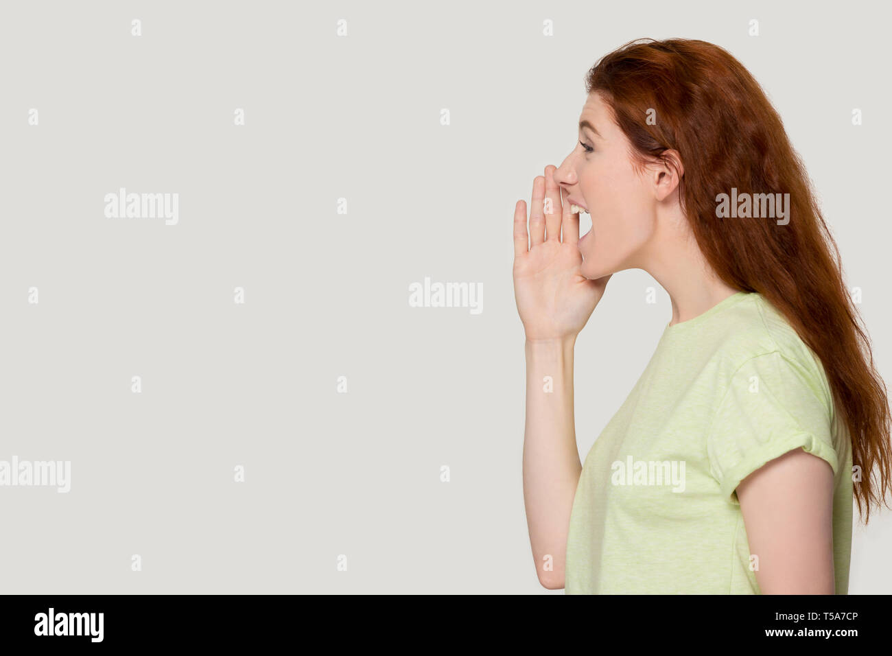 Excited redhead woman shout loudly about sale offer - Stock Image