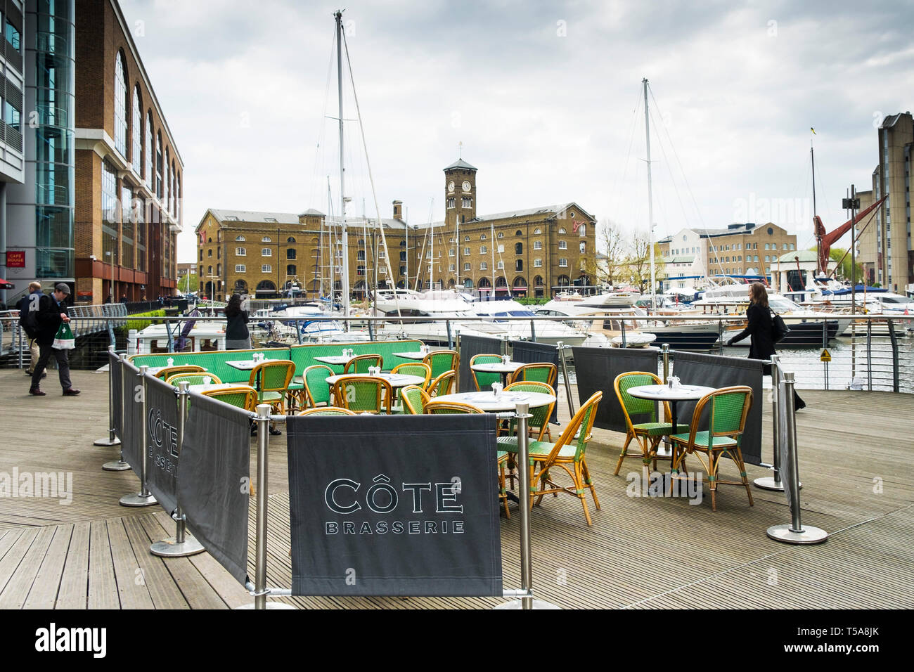 The outdoor eating area of a Cote Brasserie in St Katherine Dock; St Katherines Dock in Wapping; London. - Stock Image