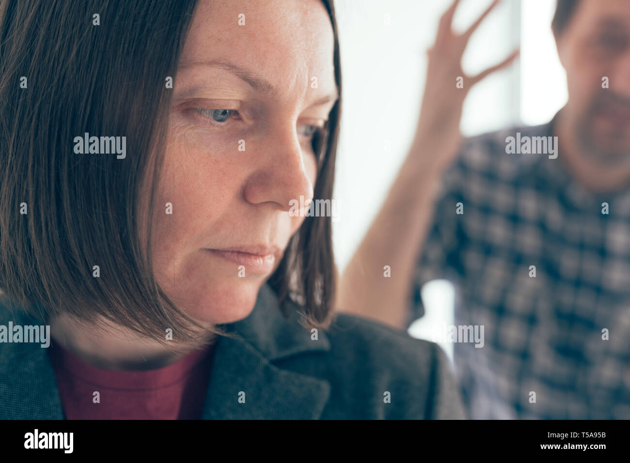 Husband and wife arguing, man yelling at woman in domestic dispute concept - Stock Image