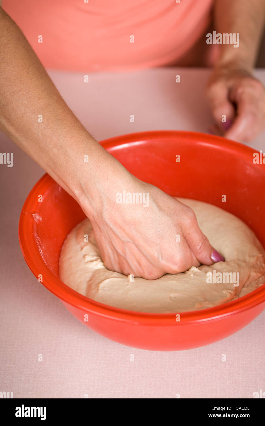 Woman punching down a bowl of naan bread, prior to forming it into the flat bread pieces to be baked. (MR) - Stock Image