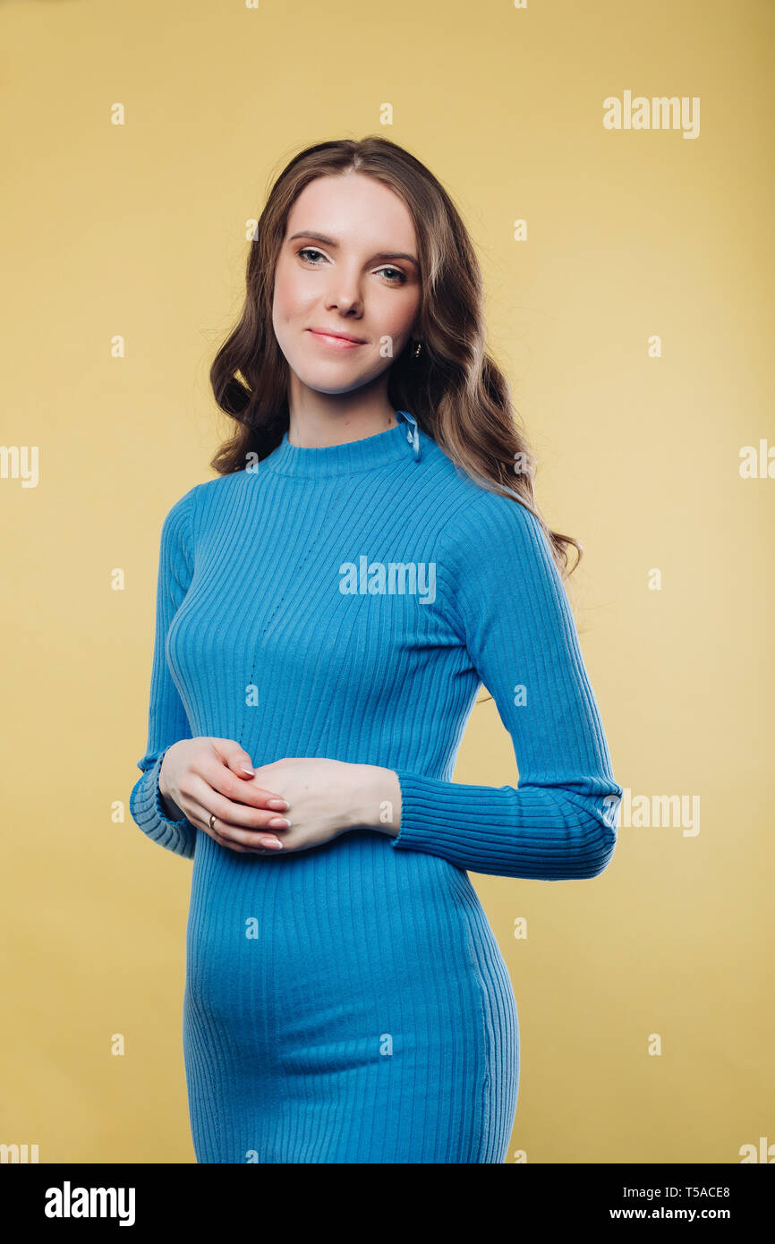 Pretty brunette woman in blue cotton dress with arms crossed on belly. - Stock Image