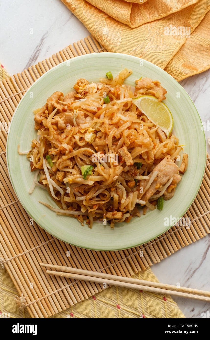 Authentic cuisine pad thai with pork rice noodles smoked tofu bean sprouts peanuts and lime garnish - Stock Image