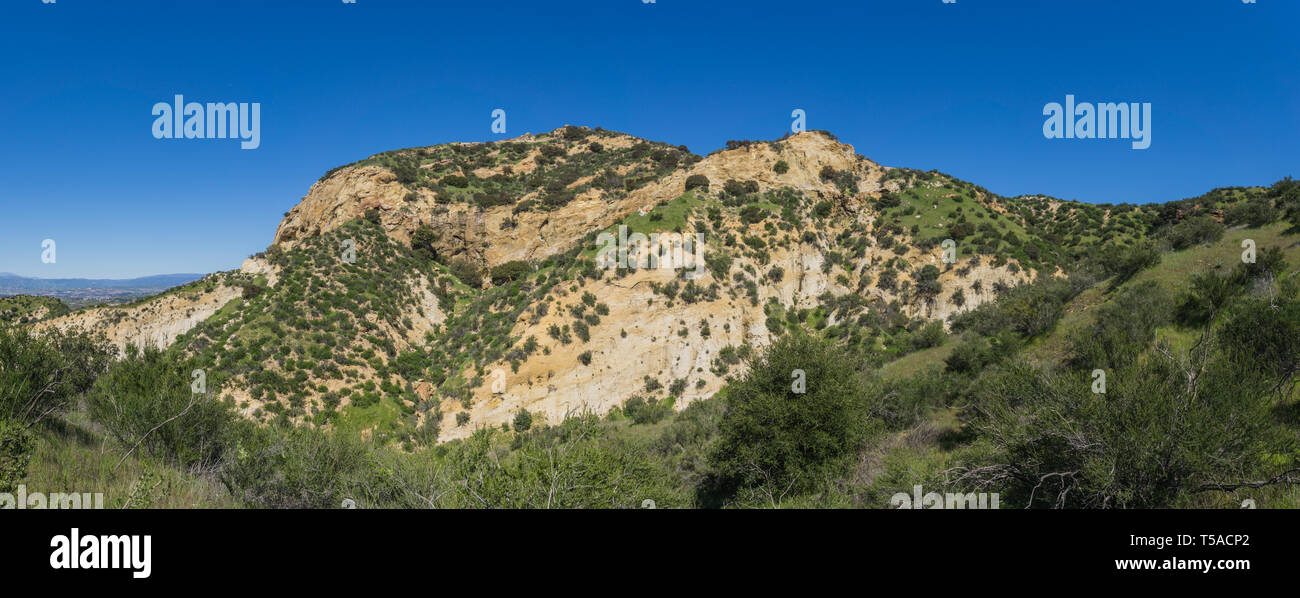 Grass covered hills lead up to the slopes of a rock canyon in California near Santa Clarita. - Stock Image