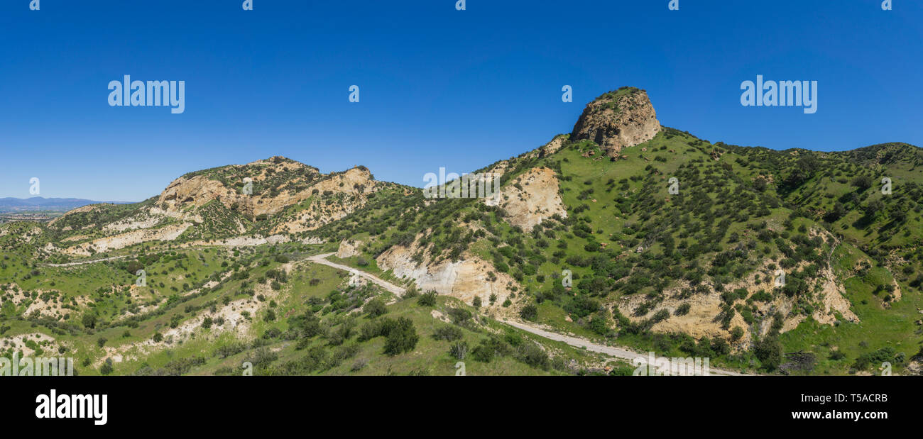 Lone hiking path winds beneath the hills of a grass covered hillside in southern California. - Stock Image