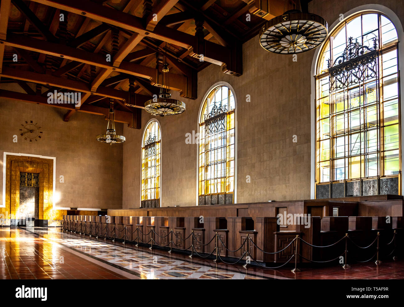 Light shining through Mission Revival windows, historic Union Station, Los Angeles, with Art Deco light fixtures hanging above former ticket counters. Stock Photo