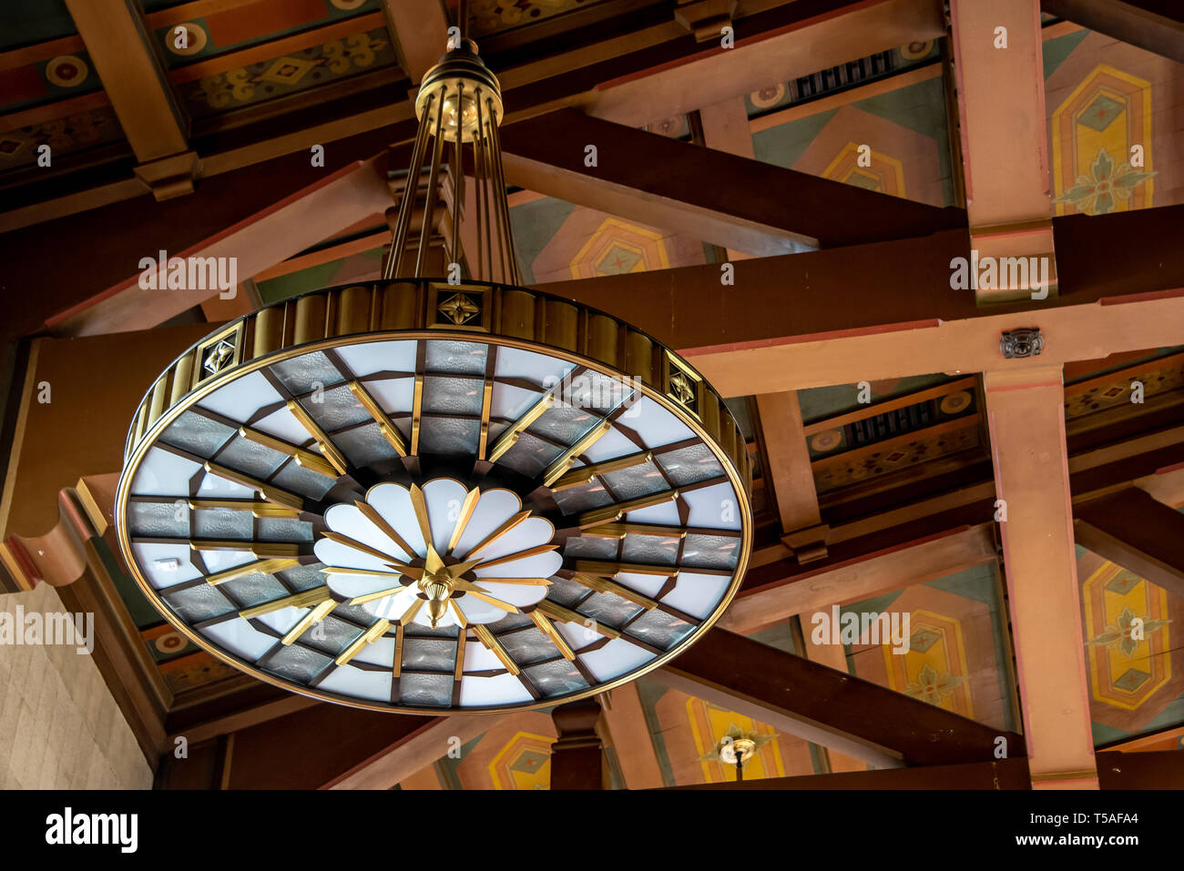 Close up of brass Art Deco light fixture in Los Angeles Union Station, train station, with details of Mission Revival painted ceiling and beams. - Stock Image