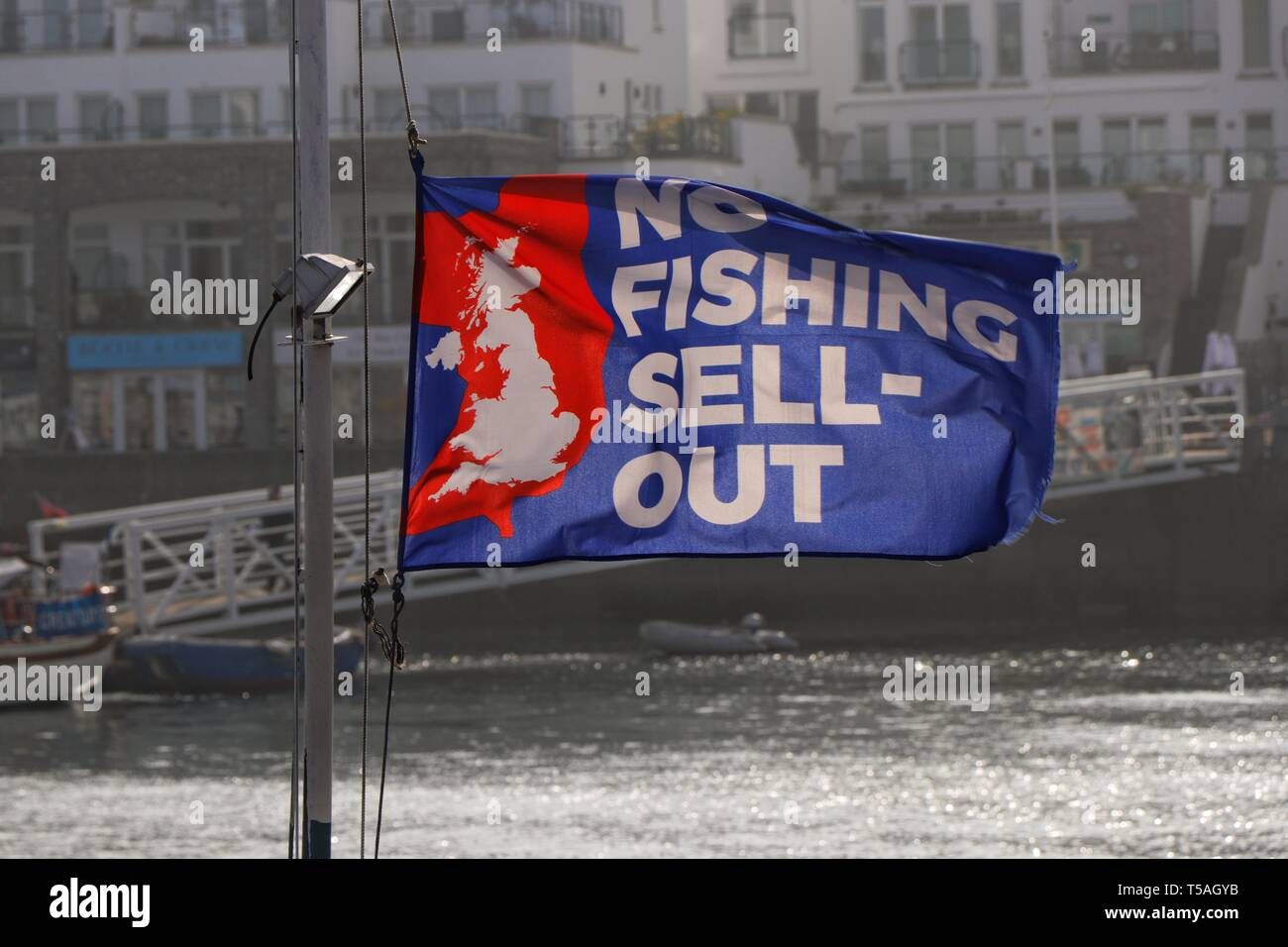 The pro Brexit message: No Fishing Sell-Out, on a bright flag fluttering in the morning breeze, Brixham Harbour, Devon, UK - Stock Image