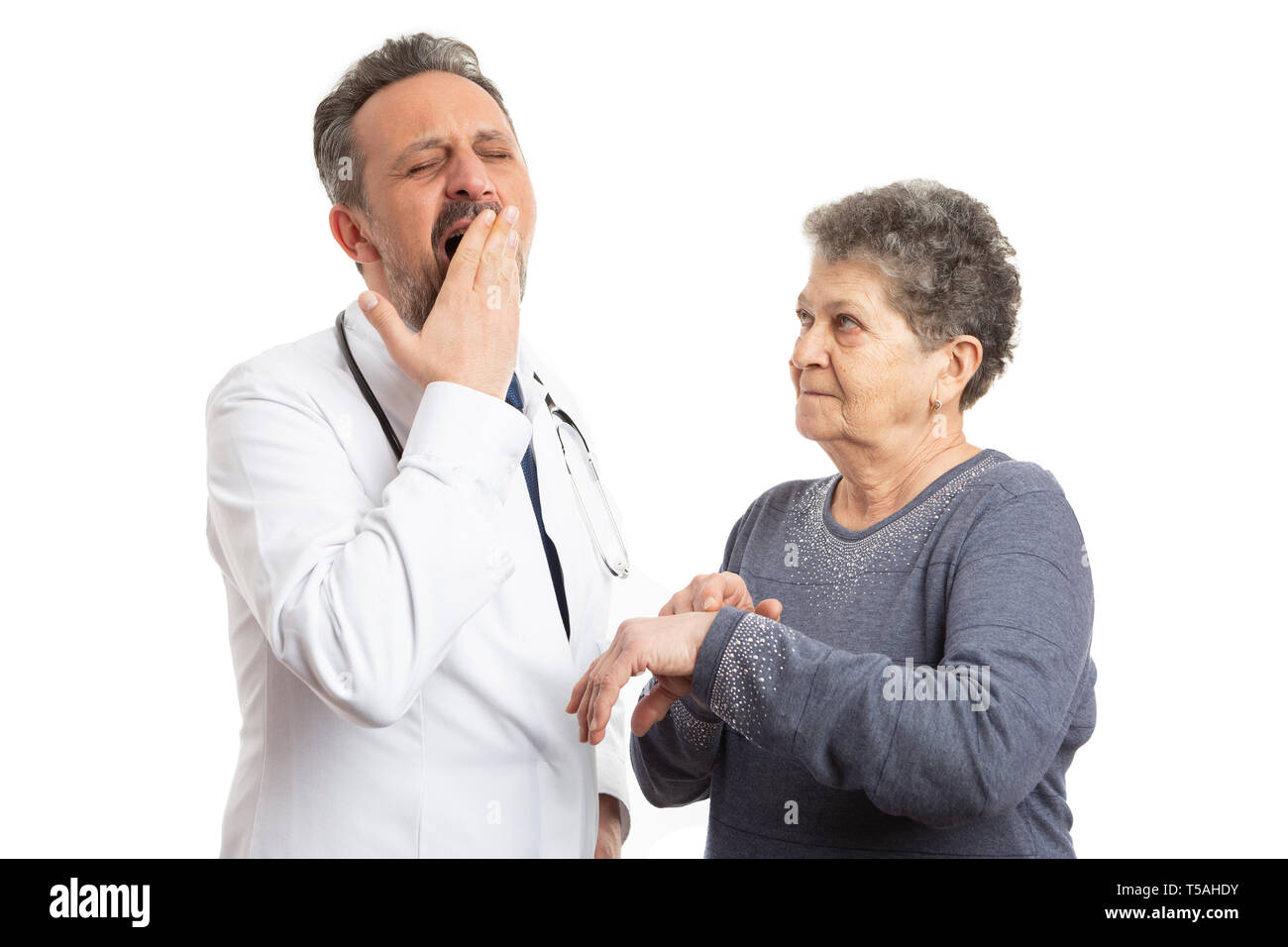 Old woman patient pointing with index finger at wrist for tired doctor yawning as late time concept isolated on white studio background - Stock Image