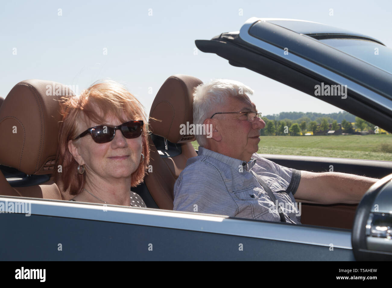 Happy senior couple with a luxury convertible car - Stock Image