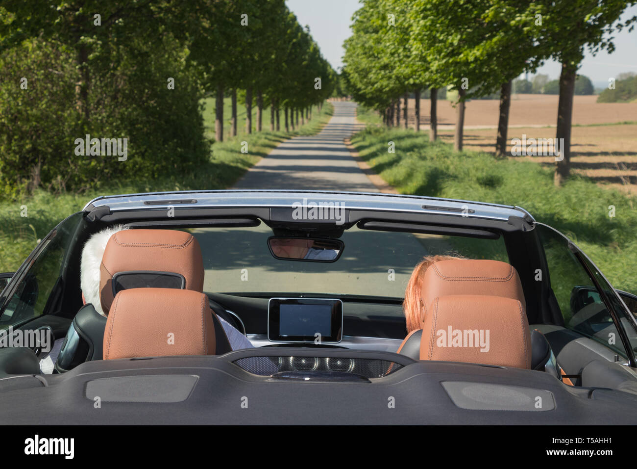 Two elderly people with a luxury convertible car - Stock Image