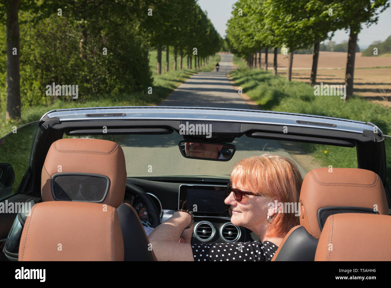 Older couple in love ride in convertible car - Stock Image