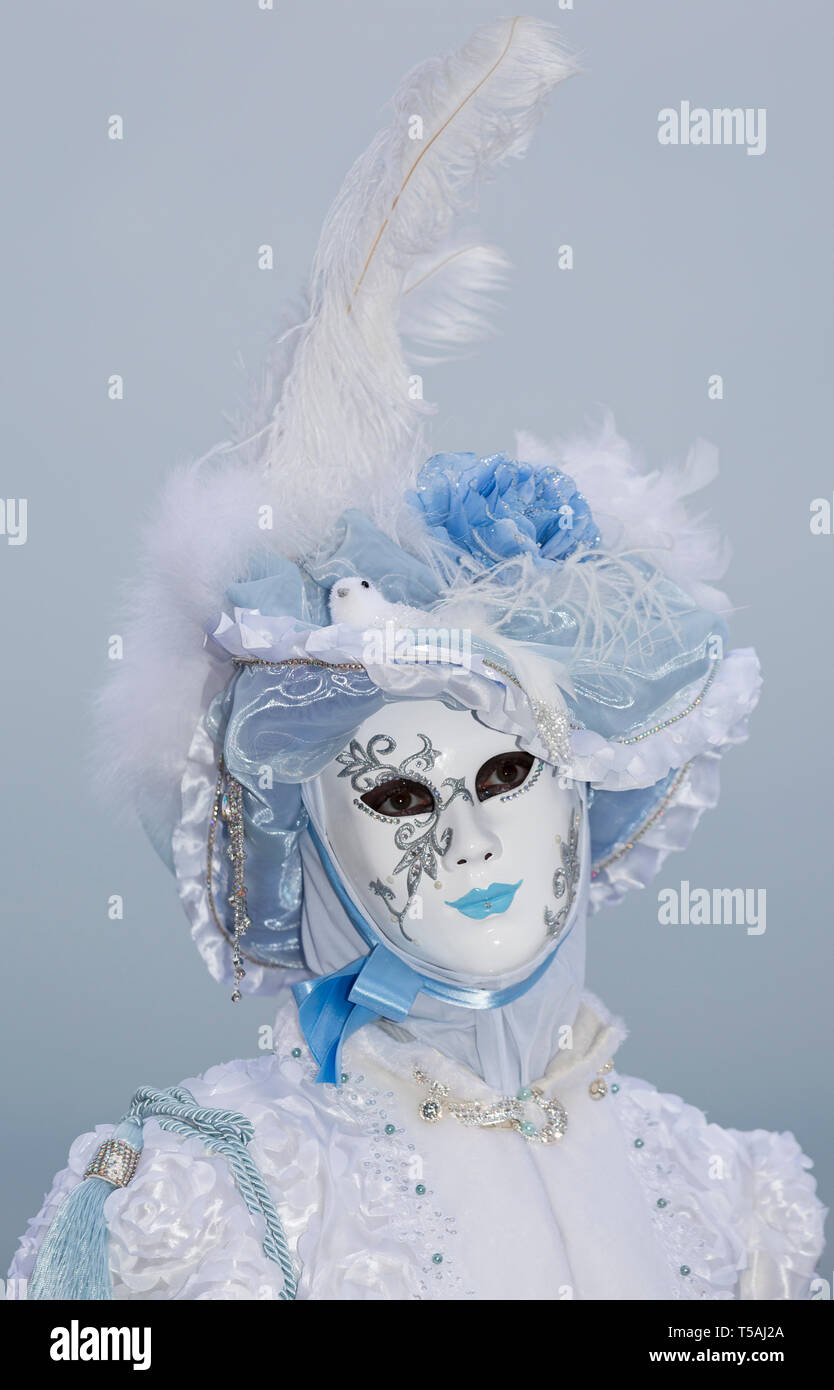 Venice carnival portrait, Italy, person wearing white mask and feather hat Stock Photo