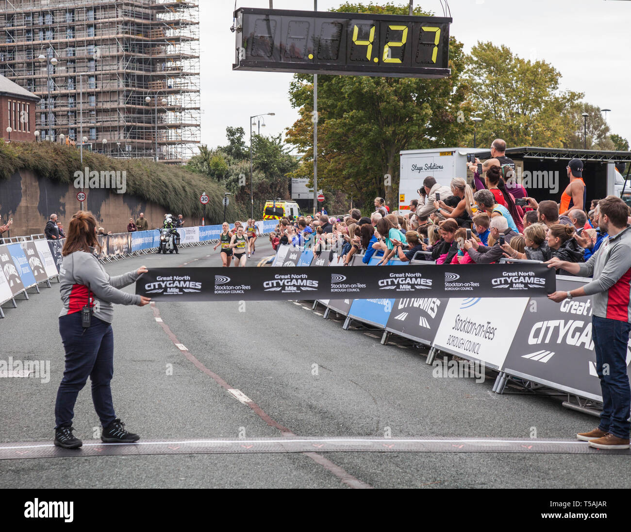Two officials hold the tape for the Woman's  Elite Mile athletes appoaching along the Riverside Road,Stockton on Tees,England,UK Stock Photo