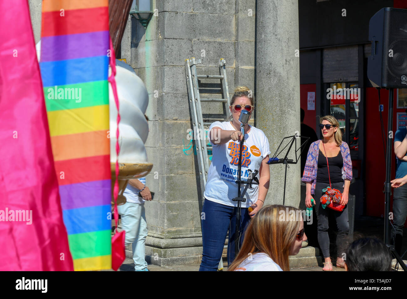 woman on the microphone talking on the charity beep beep tour. Raising Awareness for Meningitis, Brighton. Easter 2019 - Stock Image