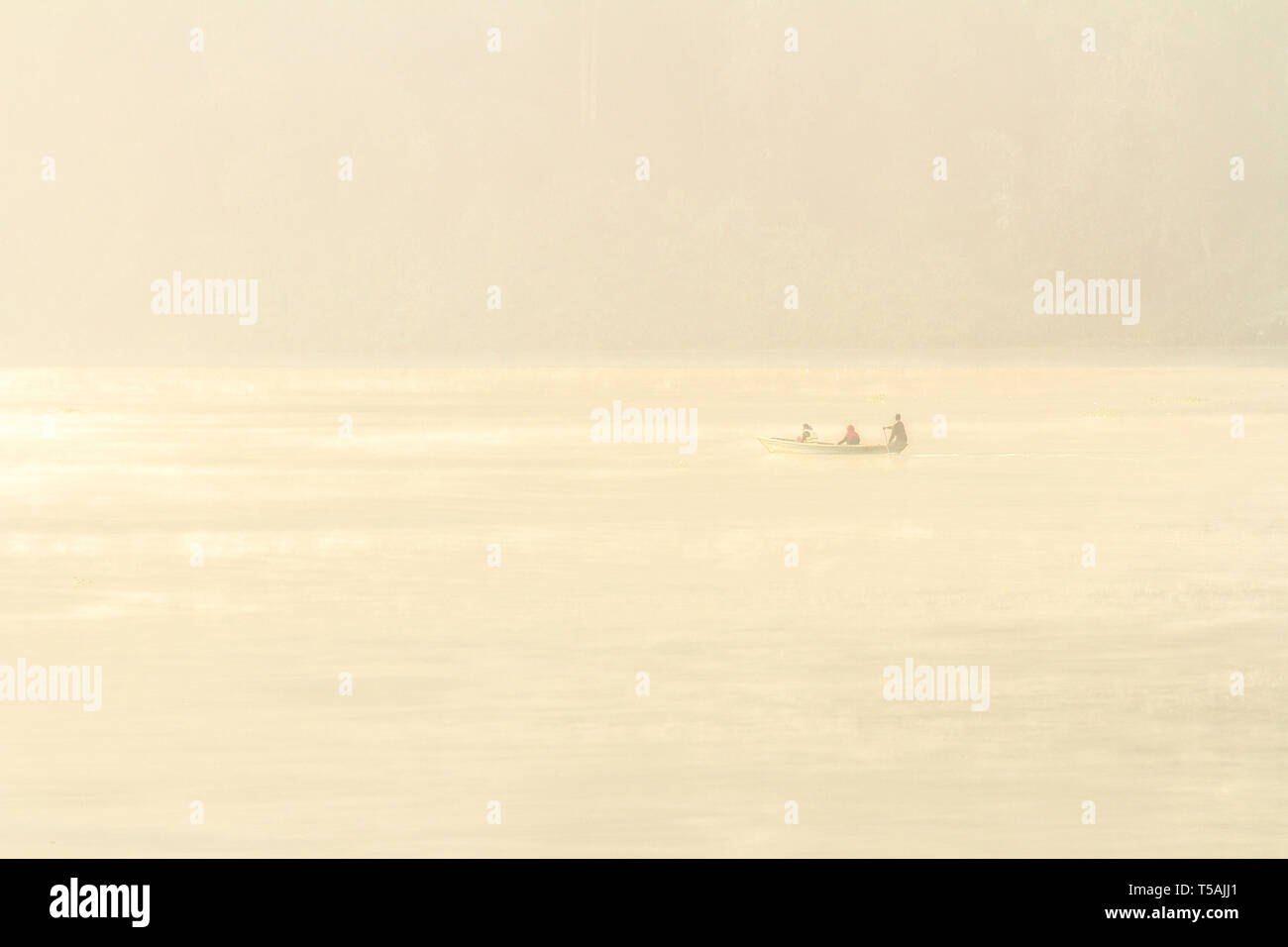 Silhouette of lonely boat rowing on the lake in the morning mist. Phewa lake, Pokhara, Nepal - Stock Image