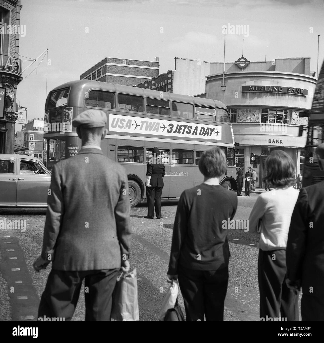 1960s, historical, people watching a policeman direct the traffic as a routemaster bus tries to do a left turn at a tube junction in North London by a branch of the Midland Bank. - Stock Image
