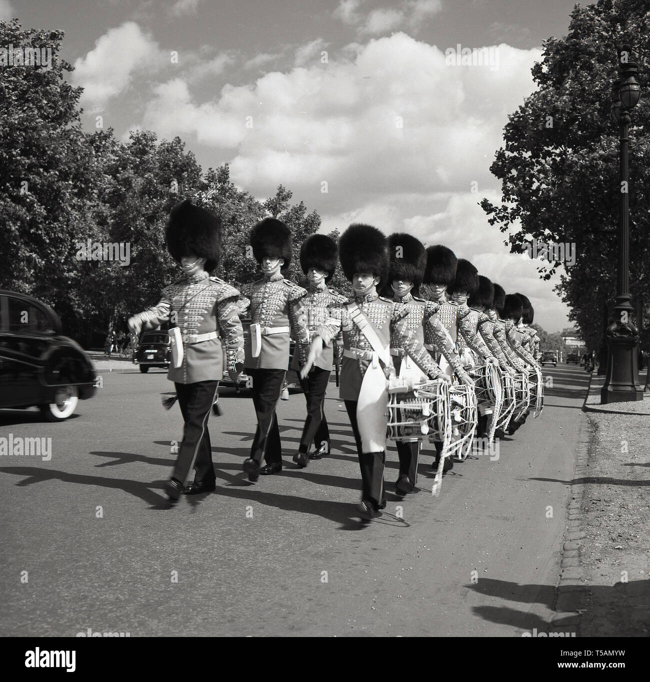 1960s, historical, 1st Battalion Grenadier Guards Corps of Drums in full uniform and bearskin helmets marching along The Mall, road between Buckingham Palace and Trafalgar Square, London, England, - Stock Image