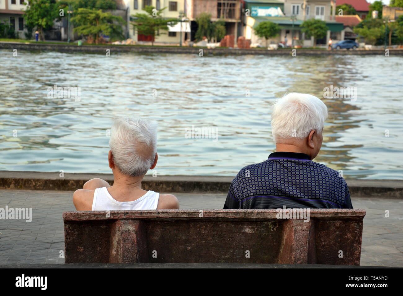Rear view of two older men sat on a bench overlooking a lake in Ha Tinh, Vietnam, in May, 2017. - Stock Image